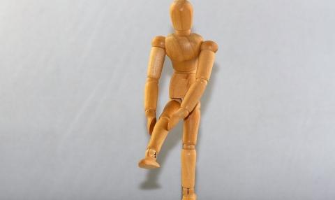 muñeco con dolor de rodilla