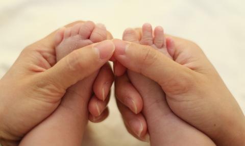 manos acariciando pies de bebes